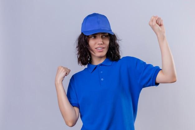 Ragazza delle consegne in uniforme blu e berretto che si rallegra del suo successo e della vittoria stringendo i pugni con gioia felice di raggiungere il suo scopo e obiettivi in piedi su bianco isolato