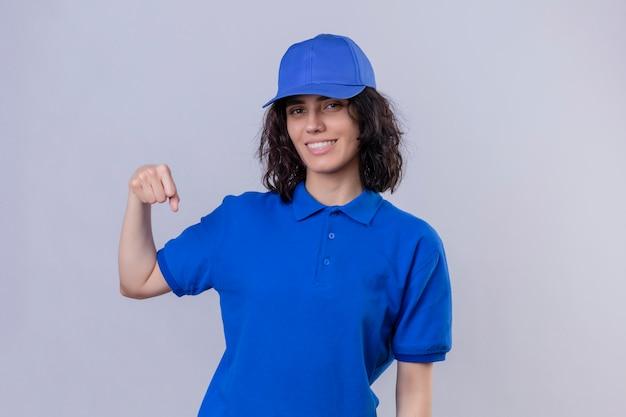 Ragazza delle consegne in uniforme blu e berretto sorridente amichevole gesticolando pugno urto come se salutasse, approvando o come segno di rispetto in piedi su bianco isolato