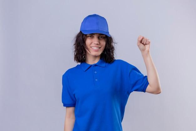 Ragazza delle consegne in uniforme blu e cappuccio che alzano il pugno dopo un concetto del vincitore di vittoria sopra lo spazio bianco isolato