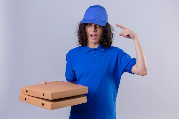 Ragazza delle consegne in uniforme blu e cappuccio che tiene le scatole della pizza che indica tempio con il dito che si concentra su un'idea che sta sul bianco