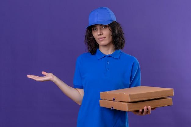 Ragazza delle consegne in uniforme blu e cappuccio che tiene le scatole della pizza e che presenta con il braccio della mano sorridente in piedi amichevole sulla porpora
