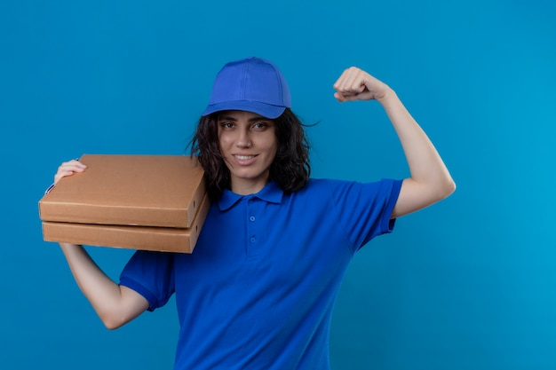 Ragazza delle consegne in uniforme blu e cappuccio che tiene le scatole per pizza che mostrano il bicipite che sorride allegramente in piedi sul blu isolato