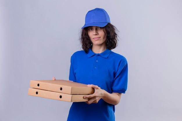 Ragazza delle consegne in uniforme blu e cappuccio che tiene le scatole per pizza sorridente in piedi sicuro
