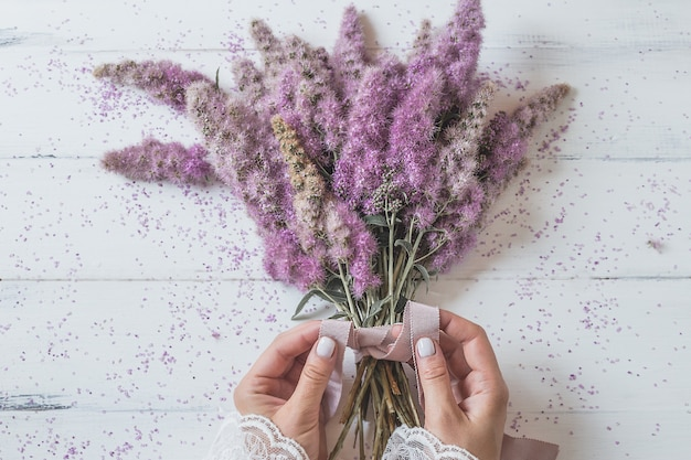 Ragazza delle mani che lega un mazzo di fiori rosa.