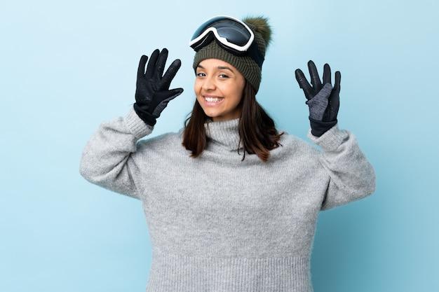 Ragazza dello sciatore della corsa mista con i vetri di snowboard sopra il blu isolato che conta nove con le dita.