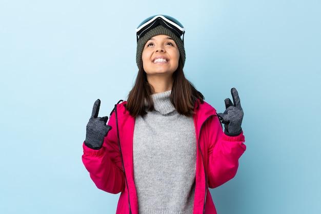 Ragazza dello sciatore della corsa mista con i vetri di snowboard sopra il blu isolato che indica su una grande idea.