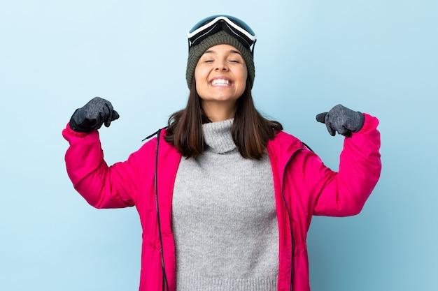 Ragazza dello sciatore della corsa mista con i vetri di snowboard sopra la parete blu isolata che fa forte gesto