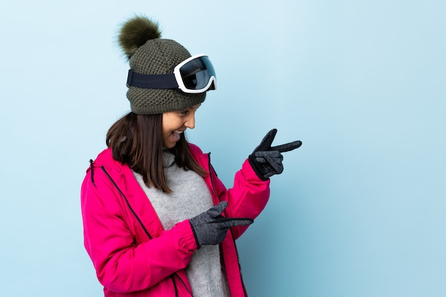 Ragazza dello sciatore della corsa mista con i vetri di snowboard sopra la parete blu isolata che indica dito il lato e che presenta un prodotto