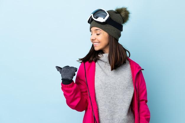 Ragazza dello sciatore della corsa mista con i vetri di snowboard sopra la parete blu isolata che indica il lato per presentare un prodotto
