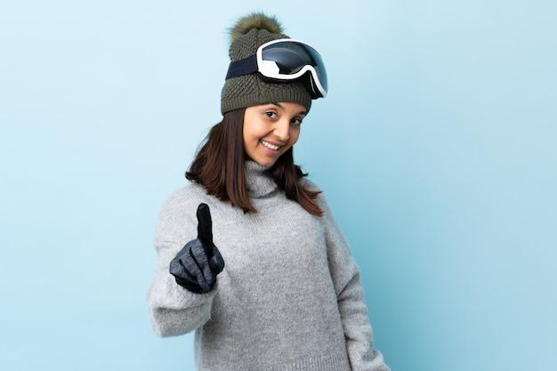 Ragazza dello sciatore della corsa mista con i vetri di snowboard sopra la parete blu isolata che mostra e che solleva un dito