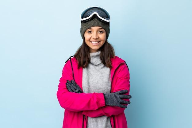 Ragazza dello sciatore della corsa mista con i vetri di snowboard sopra la parete blu isolata che tiene le armi attraversate nella posizione frontale