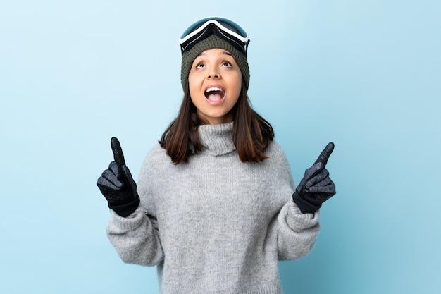 Ragazza dello sciatore della corsa mista con i vetri di snowboard sopra la parete blu isolata sorpresa e che indica su