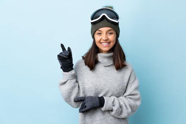 Ragazza dello sciatore della corsa mista con i vetri di snowboard su felice blu isolato e che indica su