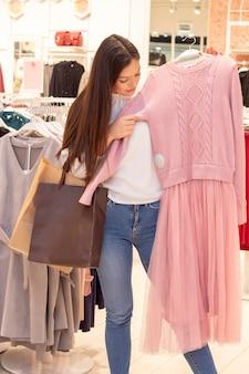 Ragazza dello shopping. una bella ragazza con lunghi capelli scuri è in una boutique di abbigliamento, sceglie un vestito per se stessa. si mette un vestito. foto verticale. nelle mani di una borsa