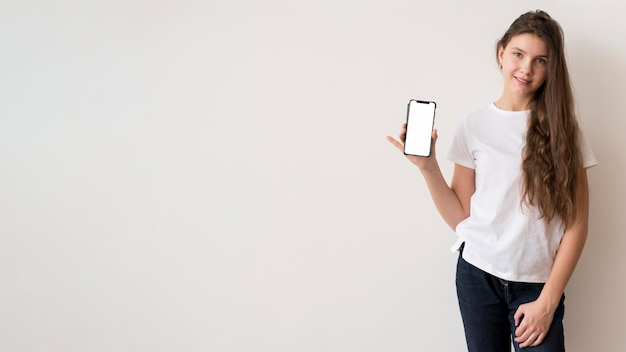 Ragazza dello spazio della copia che tiene cellulare
