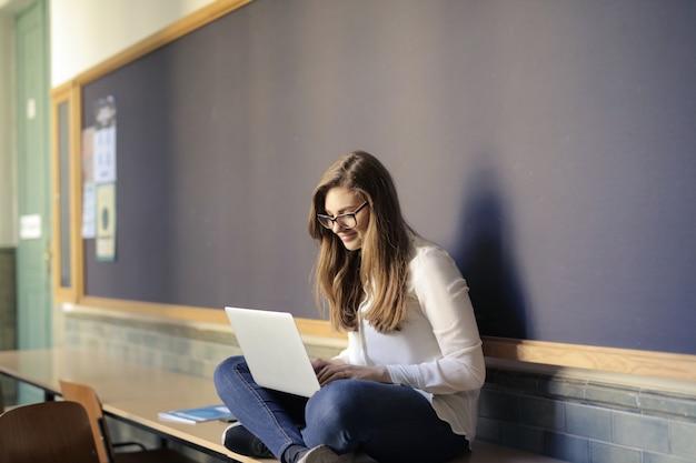 Ragazza dello studente che lavora su un computer portatile
