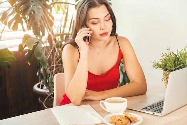 Ragazza dello studente che parla al telefono mentre sedendosi nel caffè