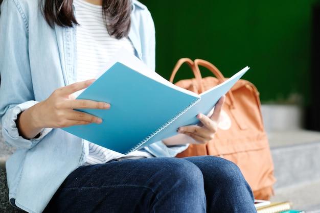 Ragazza dello studente che si siede e che legge libro, istruzione, di nuovo al concetto della scuola