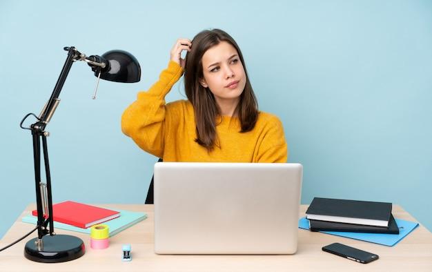 Ragazza dello studente che studia nella sua casa isolata sulla parete blu che ha dubbi mentre graffiando testa