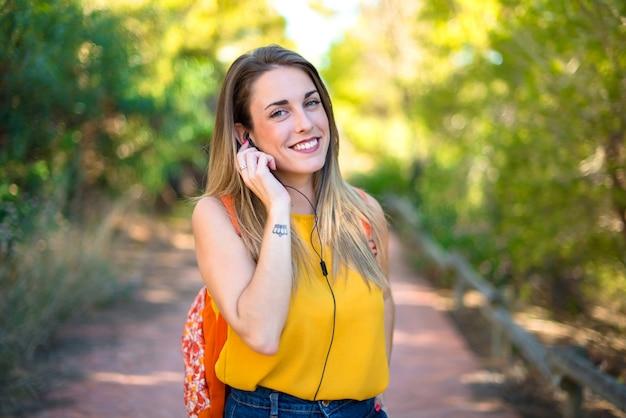 Ragazza dello studente con lo zaino in una musica d'ascolto del parco