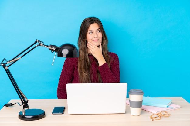 Ragazza dello studente dell'adolescente in un posto di lavoro con un computer portatile
