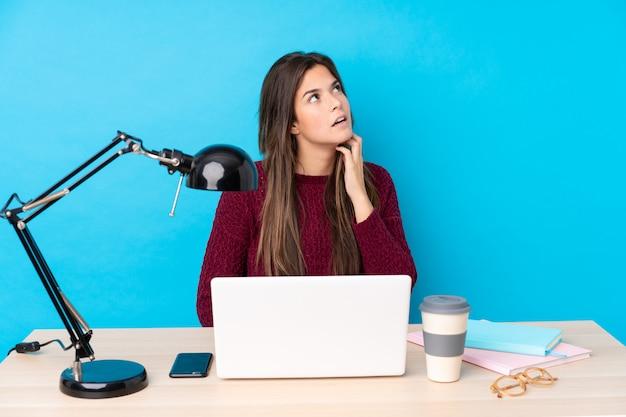 Ragazza dello studente dell'adolescente in un posto di lavoro sopra la parete blu