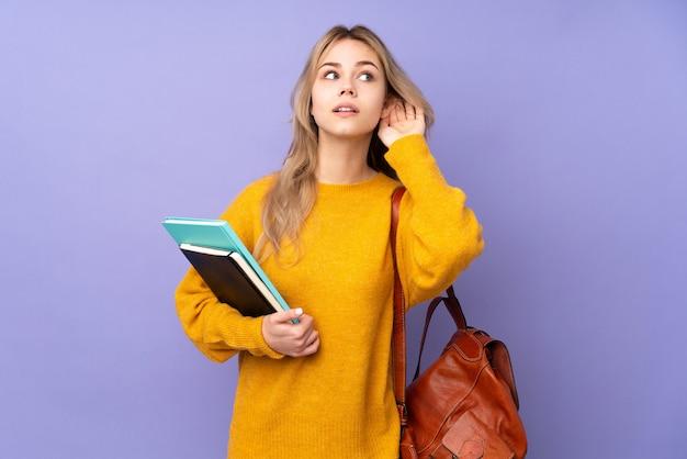 Ragazza dello studente dell'adolescente sulla parete viola che ascolta qualcosa mettendo la mano sull'orecchio
