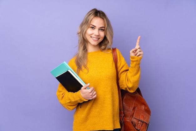Ragazza dello studente dell'adolescente sulla rappresentazione e sul sollevamento porpora un dito nel segno del meglio