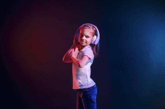 Ragazza di 7 anni che ascolta la musica in cuffie su colorato scuro. luce al neon. bambino sveglio che gode della musica da ballo felice