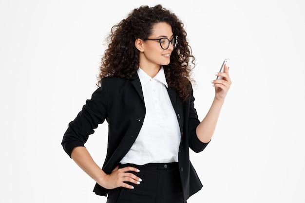 Ragazza di affari riccia allegra con gli occhiali guardando il telefono
