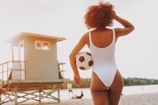 Ragazza di afro in costume da bagno sexy che osserva attraverso la spiaggia