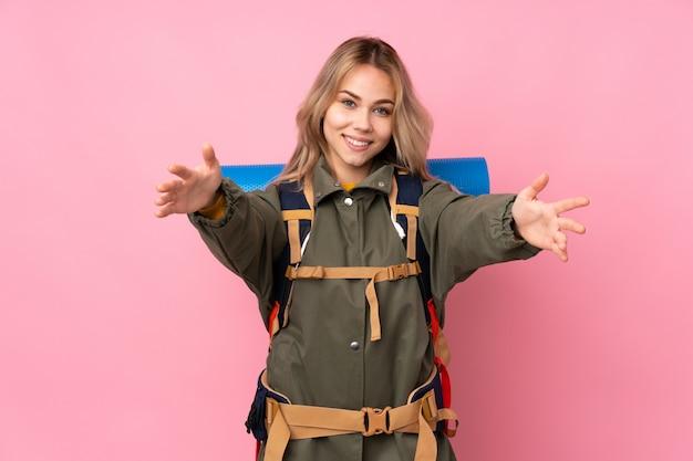 Ragazza di alpinista adolescente con un grande zaino sulla parete rosa che presenta e che invita a venire con la mano