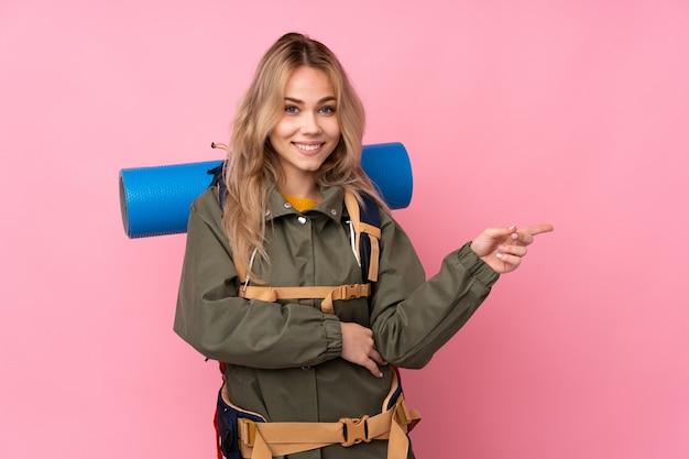 Ragazza di alpinista adolescente con un grande zaino sulla parete rosa che punta il dito verso il lato