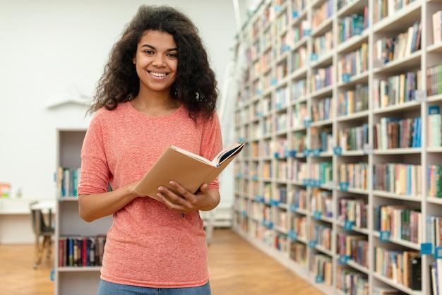 Ragazza di angolo basso alla lettura delle biblioteche