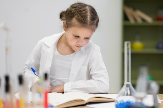 Ragazza di angolo basso che impara scienza
