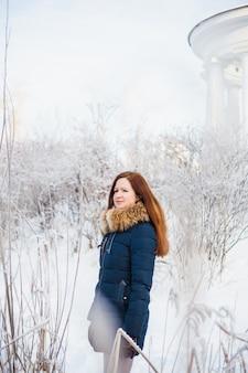 Ragazza di aspetto europeo in una passeggiata nella foresta invernale, parco, inverno e neve, salute, abiti invernali, giacca