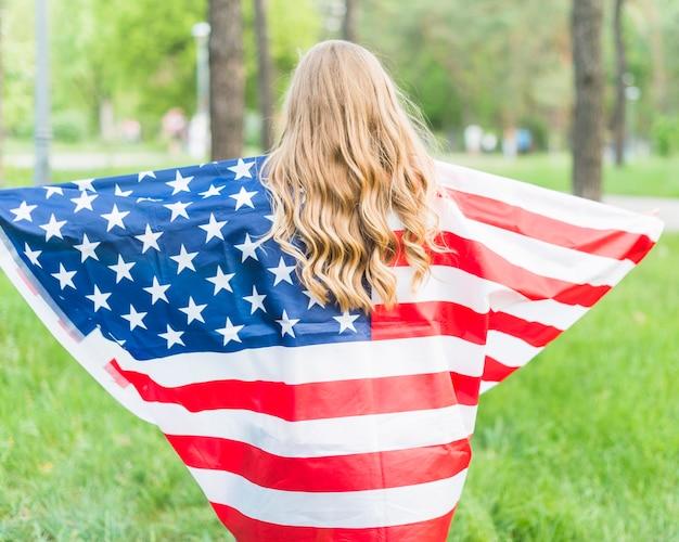 Ragazza di backview con la bandiera americana in natura
