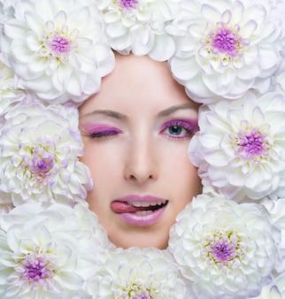 Ragazza di bellezza con fiori bianchi intorno al viso. fiori di dalia.