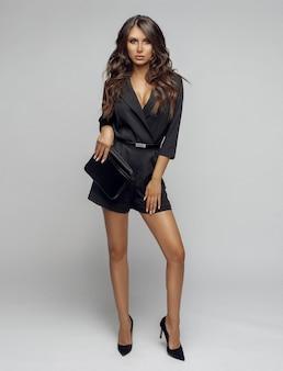Ragazza di bellezza in tuta e tacchi neri alla moda.