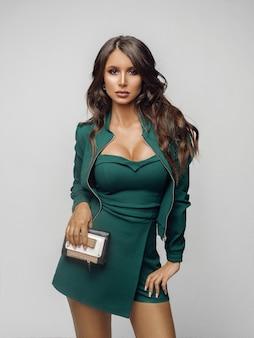 Ragazza di bellezza in tuta verde alla moda e tacchi.