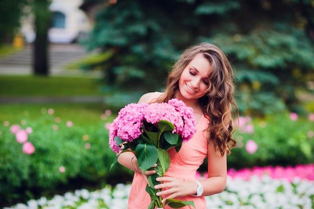 Ragazza di blogger che tiene mazzo di fiori al mercato dei fiori. concetto di blog.
