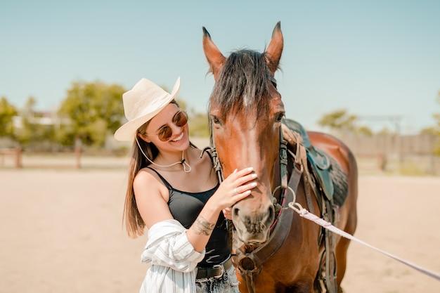Ragazza di campagna in un ranch con un cavallo marrone