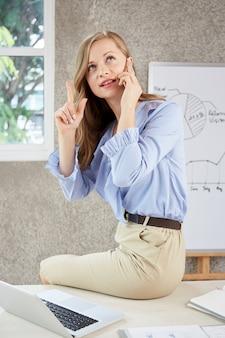 Ragazza di carriera che si siede sulla scrivania occupata parlando al telefono