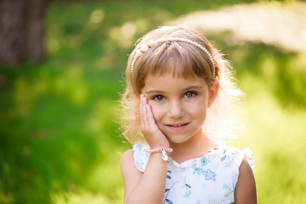 Ragazza di cinque anni dolce, felice, sorridente che pone su un'erba