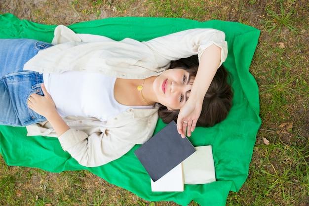 Ragazza di college spensierata pacifica felice di finire il libro di studio