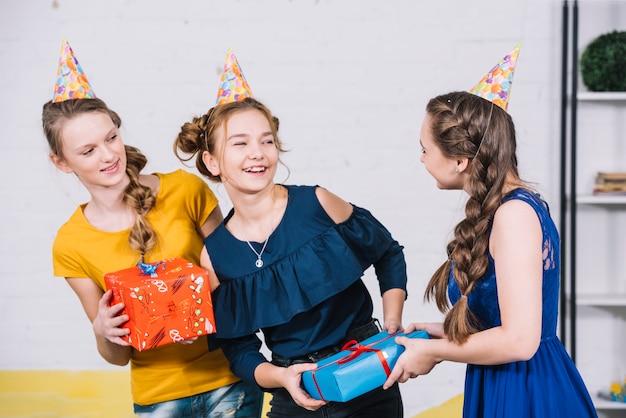 Ragazza di compleanno che riceve la confezione regalo dai suoi amici a casa
