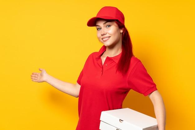 Ragazza di consegna della pizza che tiene una pizza sopra fondo isolato che estende le mani al lato per invitare a venire