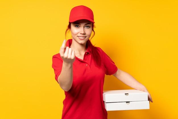 Ragazza di consegna della pizza che tiene una pizza sopra fondo isolato che fa gesto venente