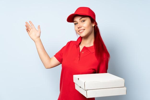 Ragazza di consegna della pizza che tiene una pizza sopra la parete isolata che estende le mani al lato per invitare a venire