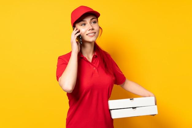 Ragazza di consegna della pizza che tiene una pizza sopra la parete isolata che mantiene una conversazione con il telefono cellulare